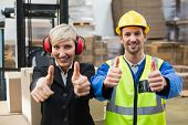 foto of warehouse  - Warehouse worker and his manager giving thumbs up in a large warehouse - JPG