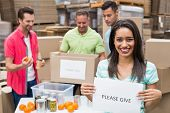 stock photo of warehouse  - Warehouse workers packing up donation boxes in a large warehouse - JPG