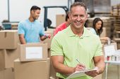 stock photo of clipboard  - Smiling volunteer man taking notes holding clipboard in a large warehouse - JPG
