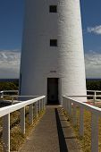 picture of lighthouse  - Image of the Handrails leading up to the Doorway of the Cape Otway Lighthouse. The door is Open and above the doorway are two square windows. Behind the Lighthouse can be seen the Sea Sky and White Clouds. - JPG