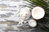 stock photo of oil well  - Coconut with coconut oil in bowl with jar of cosmetic cream on wooden background - JPG