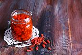 picture of doilies  - Goji berries in glass bottle on lace doily with silver spoon on rustic wooden table background - JPG