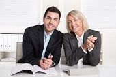 stock photo of partnership  - Happy male and female business team sitting in the office - JPG