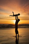 pic of father time  - Silhouette of happy father throwing his son on the beach at sunset time - JPG