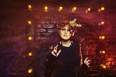 stock photo of witch  - Halloween witch with an unusual makeup and headdress of bats creates magic - JPG