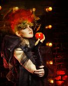stock photo of witch  - Halloween witch with an unusual makeup and headdress of bats holding an apple - JPG