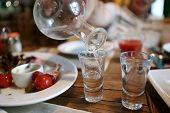 picture of vodka  - Person fills glasses of vodka in the pub - JPG