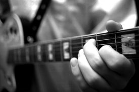 picture of musical instrument string  - a guitarist practising on his musical instrument. ** Note: Slight blurriness, best at smaller sizes - JPG