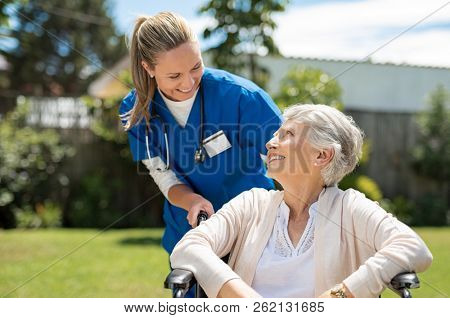 poster of Nurse taking care of old woman in wheelchair outdoor. Friendly doctor caring about elderly disabled