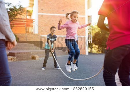 poster of Happy elementary kids playing together with jumping rope outdoor. Children playing skipping rope jum