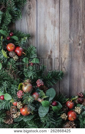 Christmas Greenery.Red Glittery Apple Ornaments And Pine Cones On Christmas Greenery On Rustic Wood Background Poster