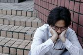 Frustrated Exhausted Asian Business Man In Depression With Hands On Face Sitting At Outdoor. poster
