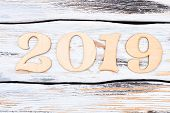 Wooden Number 2019 On Wooden Background. Cutout Wooden Digits Forming Number Of New Year 2019 On Whi poster