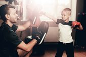 Father And Son Boxing Exercises Training In Gym. Parenthood Relationship. Sporty Family Concept. Act poster