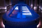 A Luxury Pillared Spa Hall With The Illuminated Plunge Pool In The Centre. An Empty Beautiful Blue-t poster