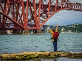Happy Vitality Woman  Spreading Her Hands In Front Of Forth Railway Bridge Edinburgh, Travel Concept poster