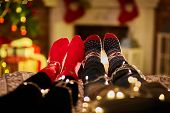 Christmas couple at home in Winter. Feet of a couple at home in Christmas time. Christmas tree and f poster
