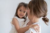 Happy Caucasian Woman Carrying Daughter And Smiling. Pretty Multiethnic Little Girl In Arms Of Mothe poster
