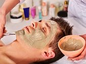 Mud facial mask of man in spa salon. Cleansing massage with clay full face. Lying man on therapy roo poster