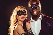 Glamorous Multiethnic Smiling Couple In Carnival Masks For New Year Party poster