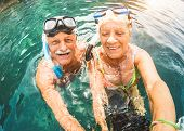 Happy Retired Couple Taking Selfie In Tropical Sea Excursion With Water Camera And Snorkel Masks - B poster