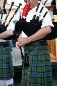 image of bagpiper  - Irish man in his kilt playing his bagpipe - JPG