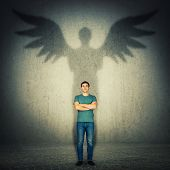 Casual Confident Man Arms Crossed. Full Length Portrait Casting A Superhero Shadow With Angel Wings  poster