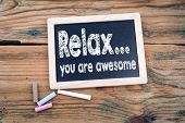 Relax, You Are Awesome. Chalkboard And Old Wooden Table With Texture poster