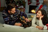 Christmas couple at home in Winter. Happy young couple lying on floor at home with dog Christmas tim poster