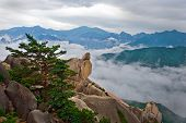 Hanging stone at the Ulsanbawi Rock against the fog seorak mountains at the Seoraksan National Park,
