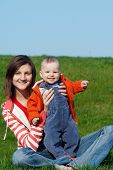 picture of mother baby nature  - Happy mother with son sitting on green grass - JPG