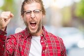 Young handsome man with long hair wearing glasses over isolated background angry and mad raising fis poster