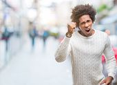 Afro american man over isolated background angry and mad raising fist frustrated and furious while s poster