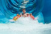 Boy Having Fun On The Water Slide On Floater In The Aqua Fun Park. poster