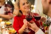 holidays and celebration concept - close up of happy friends having christmas dinner at home, drinki poster
