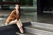 Young Businesswoman Sitting Outside Of Office Building. Beautiful Woman Wearing Formal Wear. Young G poster