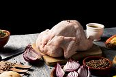 closeup of a rustic wooden table full of ingredients to prepare a stuffed turkey, such as a raw turk poster