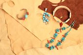 pic of chokers  - Assortment of Native American silver turquoise and coral jewelry displayed on pieces of soft and pliable buckskin and leather - JPG