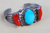 stock photo of buckskin  - Native American Silver bracelet with turquoise and coral inset laying on piece of soft pliable buckskin leather - JPG