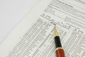 stock photo of nyse  - NYSE New York Stock Exchange on paper with pen at financial pages - JPG