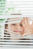Happy child peeking through window blinds