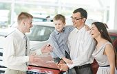 Car salesperson demonstrating new automobile to young family with child