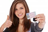 Attractive teenage girl proudly showing her driver's license. All on white background.