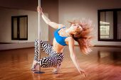 foto of pole dancer  - young pretty girl pole dancing in a dance hall - JPG