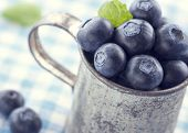 picture of hazy  - Closeup of fresh blueberries in an old metal cup with green leaves on a blue tablecloth with vintage hazy editing - JPG