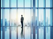 picture of wall cloud  - Businessman is standing in sunny office and looking city through window - JPG