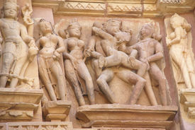 image of kandariya mahadeva temple  - Sculptures of loving couples illustrating the Kama Sutra on walls of Kandariya Mahadeva Temple at Khajuraho in India Asia - JPG