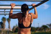 picture of athletic  - young athletic fitness woman working out at outdoor gym doing pull ups at sunrise - JPG