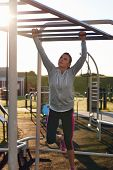 stock photo of pull up  - young athletic fitness woman working out at outdoor gym doing pull ups at sunrise - JPG