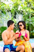stock photo of all-inclusive  - Asian couple drinking fancy cocktails at hotel or club pool - JPG
